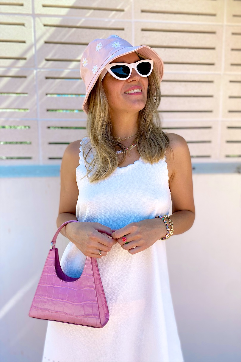 Floral Bucket Hat. Fashion and Style Blog Girl from Heartfelt Hunt. Girl with blonde hair wearing a floral bucket hat, white summer dress, white sunglasses, pink Staud bag and pink sandals.