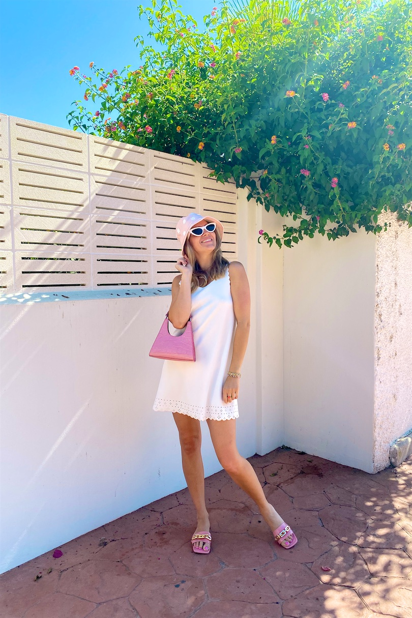 Floral Bucket Hat. Fashion Blogger Girl by Style Blog Heartfelt Hunt. Girl with blond hair wearing a floral bucket hat, white summer dress, white sunglasses, pink Staud bag and pink sandals.