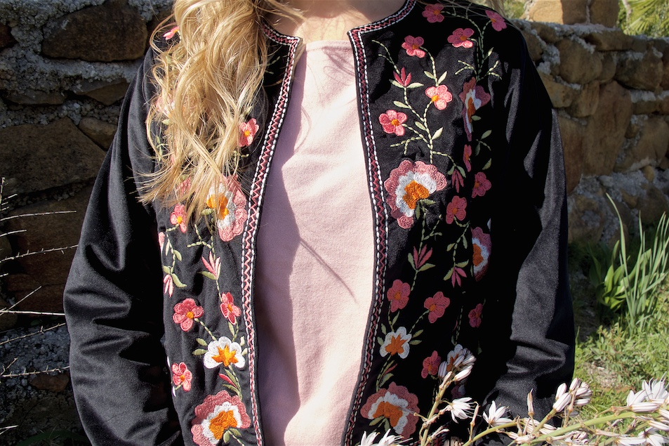 Floral Embroidery. Fashion and Style Blog Girl from Heartfelt Hunt. Girl with blonde, loose curls wearing a jacket with floral embroidery, pink sweater, black jeans and studded boots.
