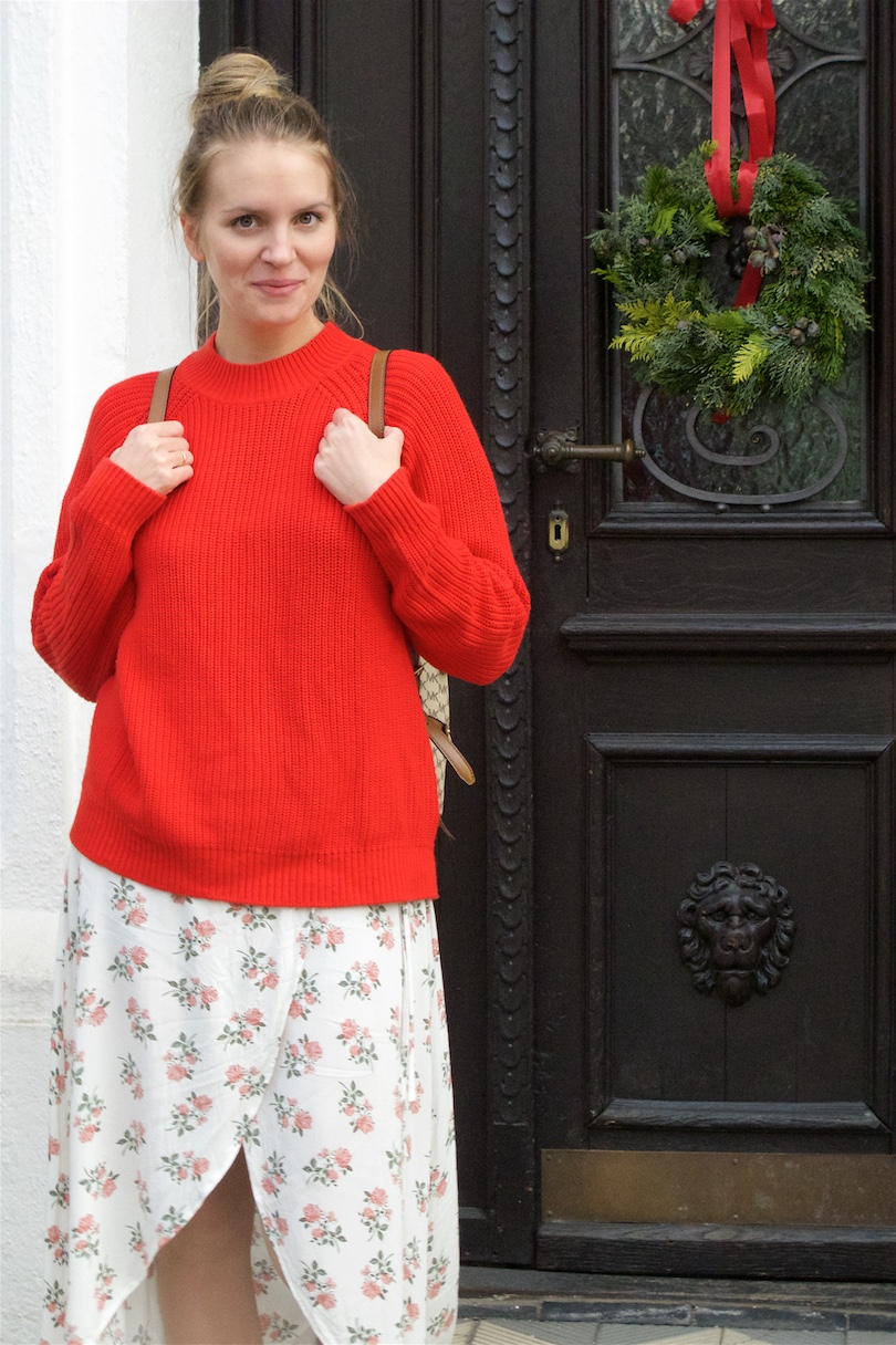 Floral Holiday Season Look. Fashion Blogger Girl by Style Blog Heartfelt Hunt. Girl with blond, high messy bun wearing a floral dress, red sweater, Michael Kors backpack and booties.