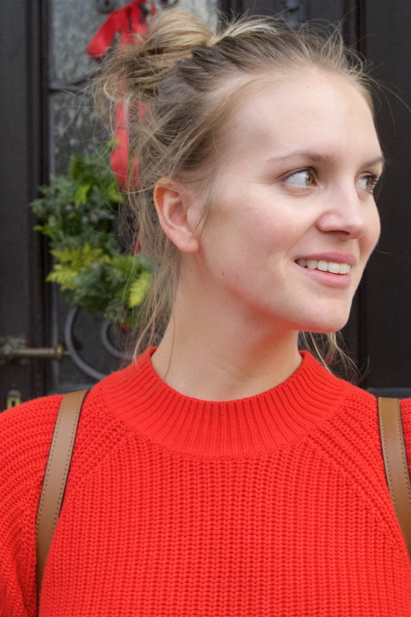 Floral Holiday Season Look. Fashion and Style Blog Girl from Heartfelt Hunt. Girl with blonde, high messy bun wearing a floral dress, red sweater, Michael Kors backpack and booties.