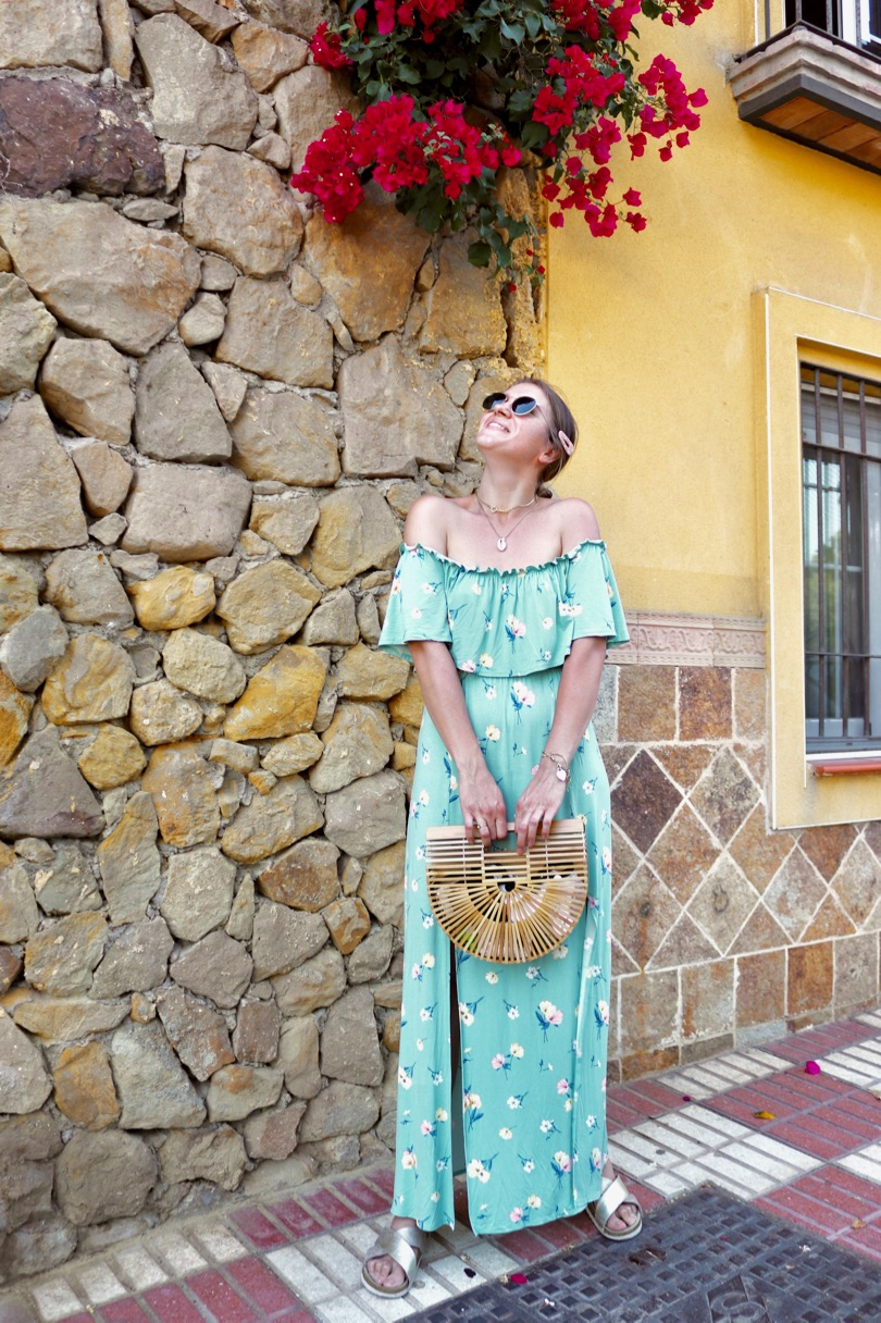 Floral Maxi Dress. Fashion Blogger Girl by Style Blog Heartfelt Hunt. Girl with blond low bun and pink hair clip wearing a floral maxi dress, Ray-Ban sunglasses, bamboo bag and golden sandals.