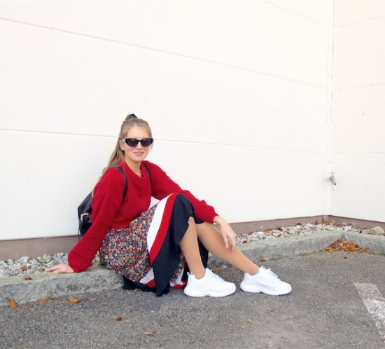 Floral Midi Skirt. Fashion Blogger Girl by Style Blog Heartfelt Hunt. Girl with blond half-up half-down messy bun wearing a red sweater, floral midi skirt, Rebecca Minkoff backpack, scrunchie, slim sunglasses and chunky sneakers.