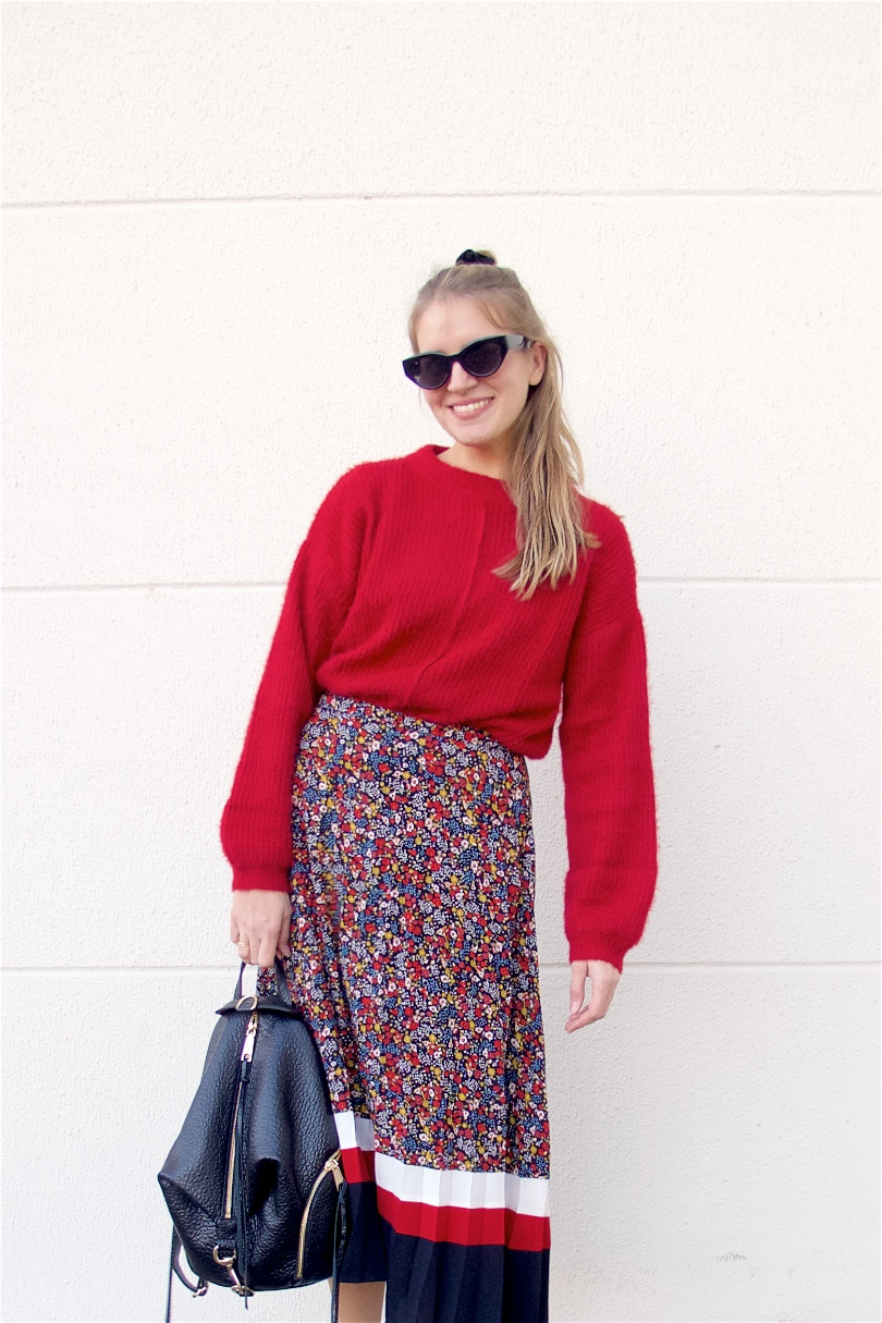 Floral Midi Skirt. Fashion and Style Blog Girl from Heartfelt Hunt. Girl with blonde half-up half-down messy bun wearing a red sweater, floral midi skirt, Rebecca Minkoff backpack, scrunchie, slim sunglasses and chunky sneakers.