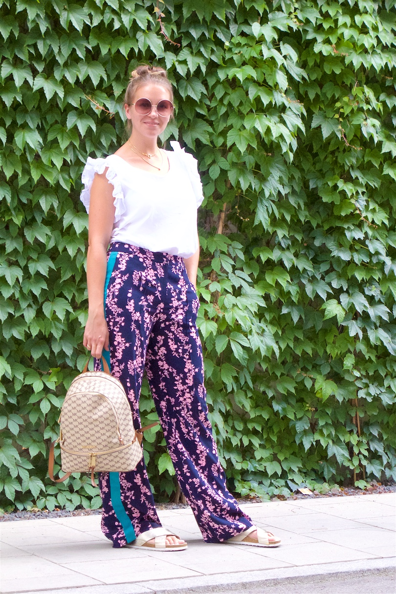 Floral Pants. Fashion and Style Blog Girl from Heartfelt Hunt. Girl with blonde, high messy bun wearing floral pants, ruffled top, Michaels Kors backpack and golden sandals.