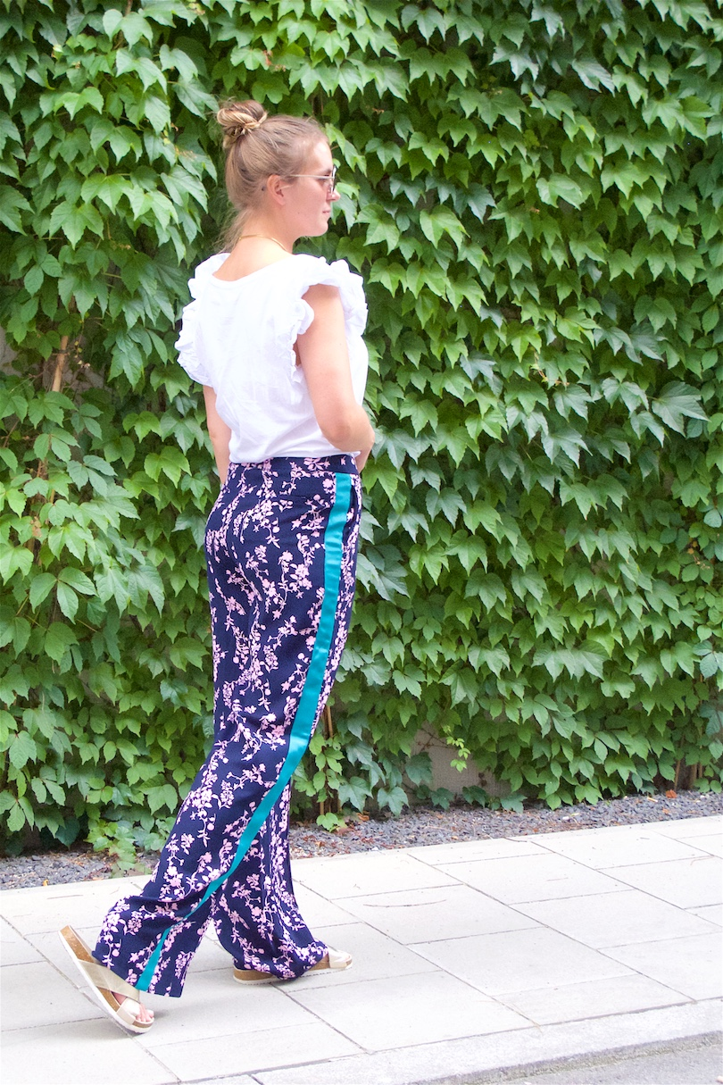 Floral Pants. Fashion Blogger Girl by Style Blog Heartfelt Hunt. Girl with blond, high messy bun wearing floral pants, ruffled top, Michaels Kors backpack and golden sandals.