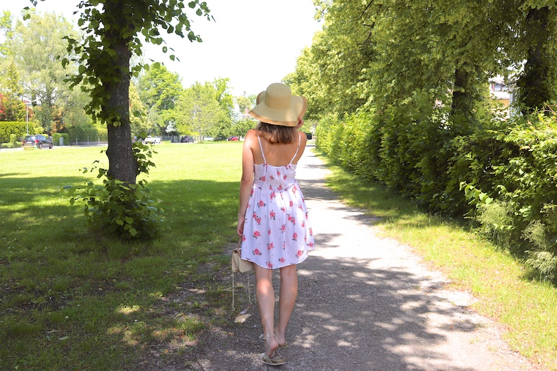 Floral Summer Dress. Fashion Blogger Girl by Style Blog Heartfelt Hunt. Girl with blond hair wearing a floral summer dress, floppy straw hat, Ray-Ban sunglasses, straw bag and golden sandals.