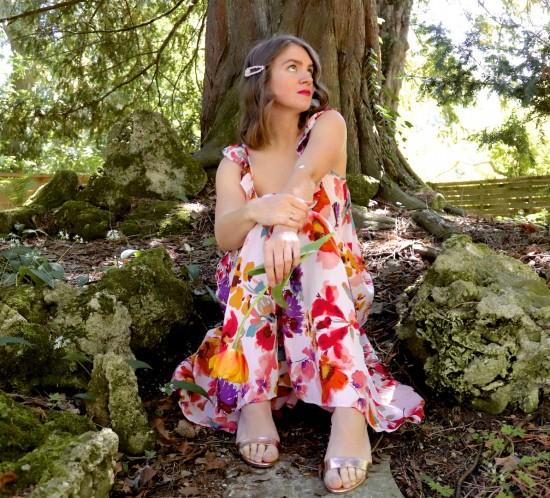 Flower Dress. Fashion Blogger Girl by Style Blog Heartfelt Hunt. Girl with blond loose waves and rhinestone hair clip wearing a flower dress, rhinestone earrings, metallic clutch, metallic heels.