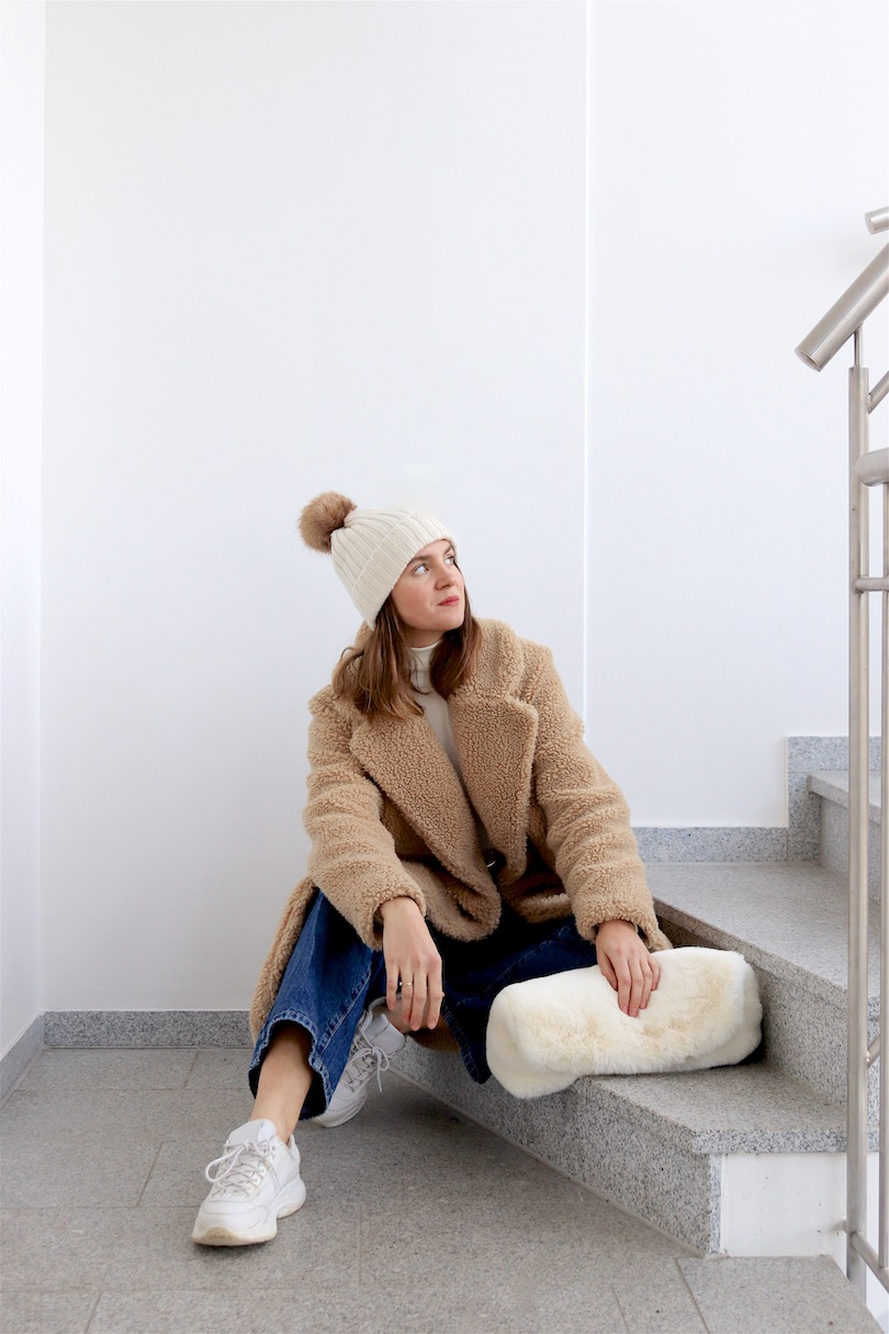 Fluffy Winter. Fashion Blogger Girl by Style Blog Heartfelt Hunt. Girl with blond hair wearing a teddy coat, white turtleneck, denim, pompom beanie, fluffy faux fur bag and white sneakers.