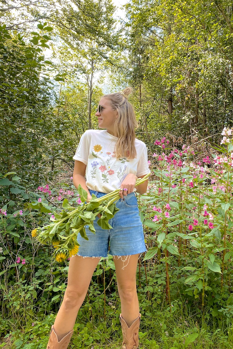 Forest Flowers. Fashion Blogger Girl by Style Blog Heartfelt Hunt. Girl with blond half-up half-down hairstyle with scrunchie wearing a forest flower tee, denim shorts, Ray-Ban sunglasses and cowboy boots.