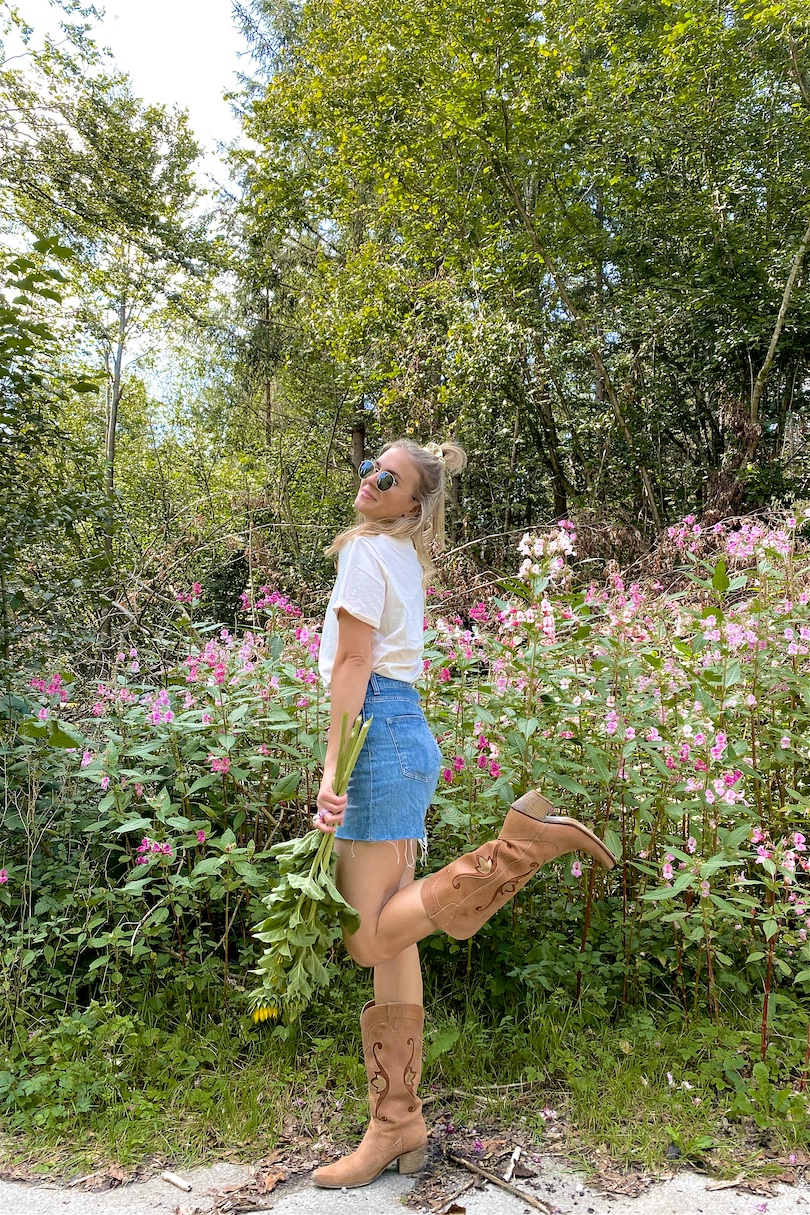 Forest Flowers. Fashion and Style Blog Girl from Heartfelt Hunt. Girl with blonde half-up half-down hairstyle with scrunchie wearing a forest flower tee, denim shorts, Ray-Ban sunglasses and cowboy boots.