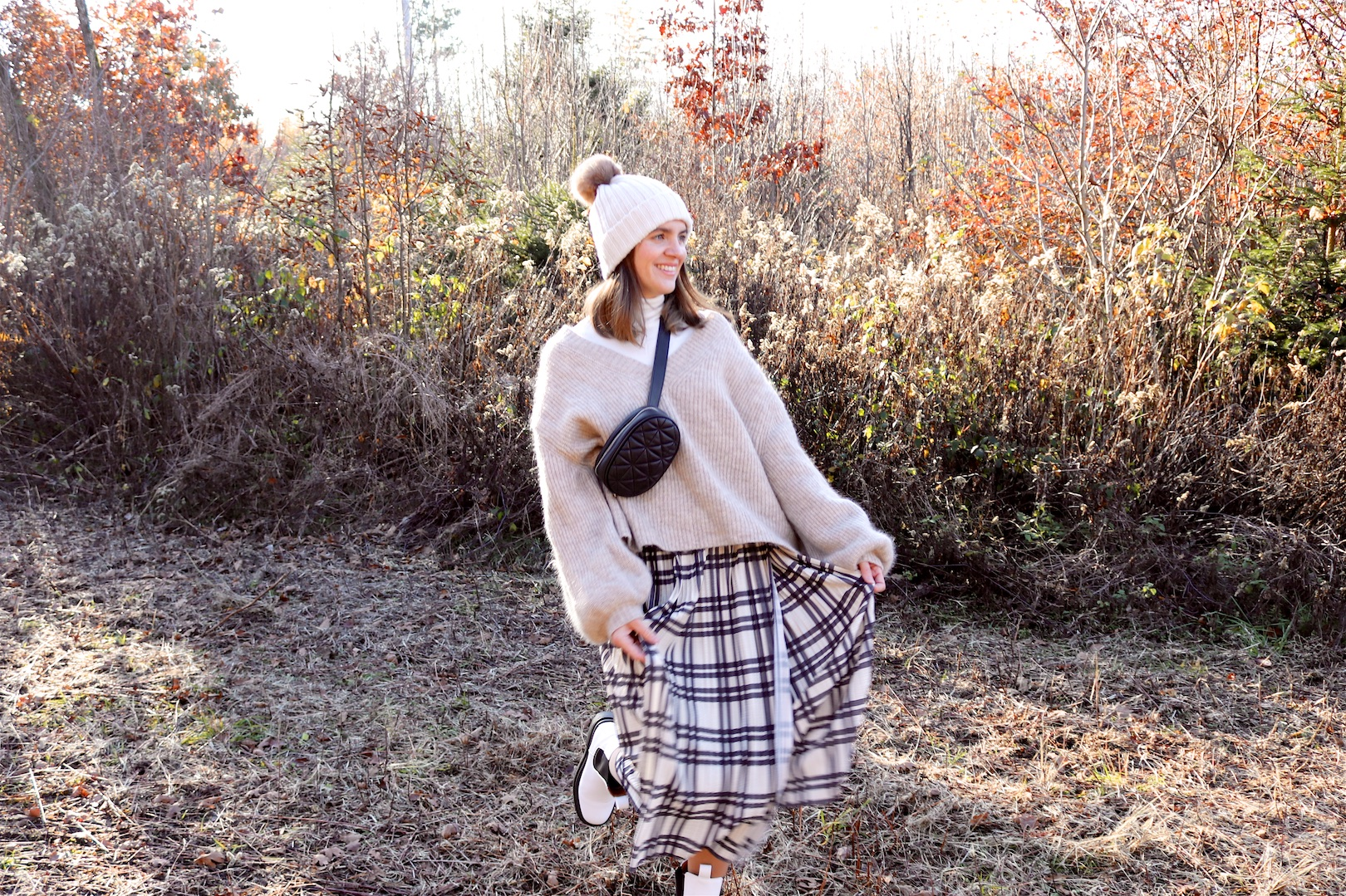 Forest Walk. Fashion and Style Blog Girl from Heartfelt Hunt. Girl with blonde hair wearing a pompom beanie, white turtleneck, chunky sweater, pleated skirt, belt bag and white boots.
