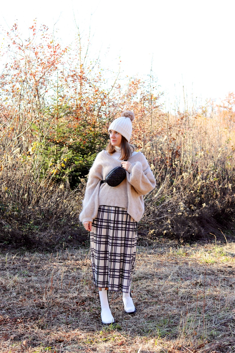 Forest Walk. Fashion Blogger Girl by Style Blog Heartfelt Hunt. Girl with blond hair wearing a pompom beanie, white turtleneck, chunky sweater, pleated skirt, belt bag and white boots.