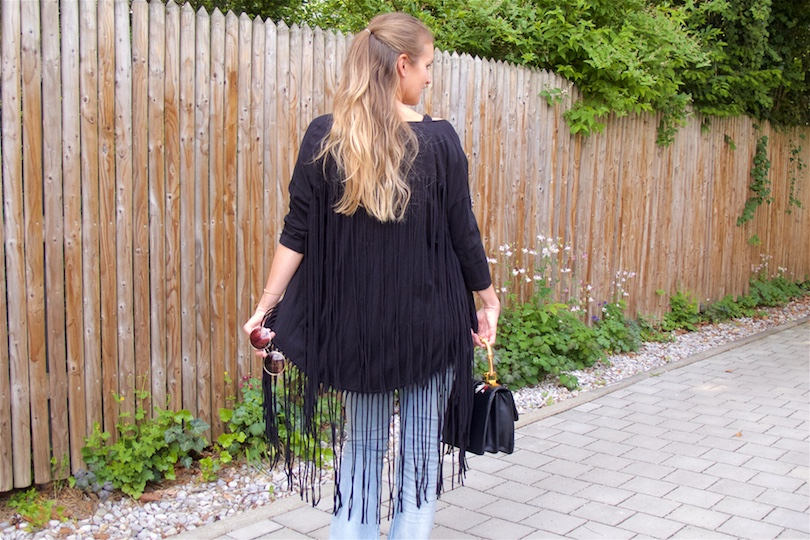 Fringe Jacket. Fashion Blogger Girl by Style Blog Heartfelt Hunt. Girl with blond half-up half-down hairstyle wearing a fringe jacket, black top, destroyed jeans, floral bag and shoes.