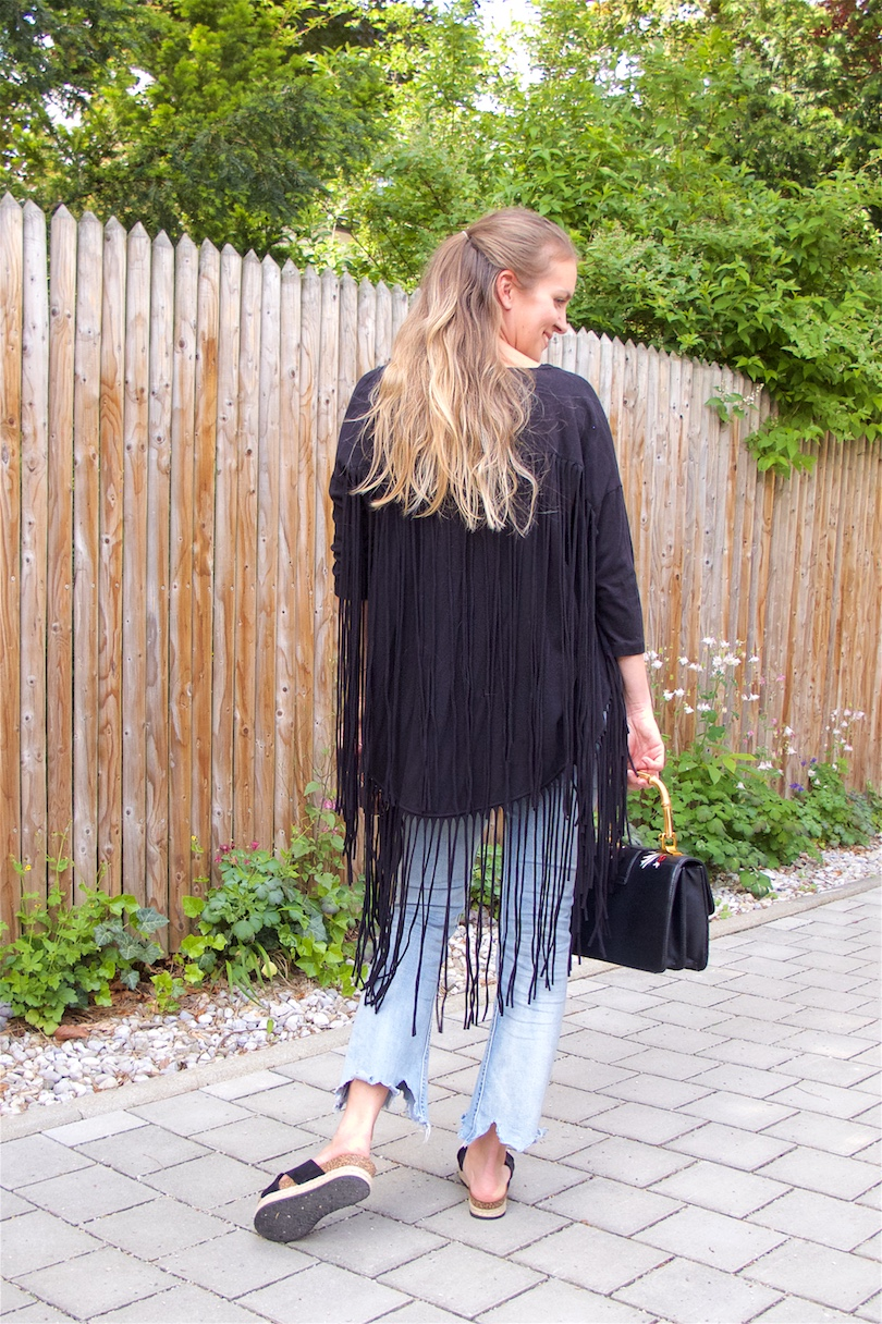 Fringe Jacket. Fashion and Style Blog Girl from Heartfelt Hunt. Girl with blonde half-up half-down hairstyle wearing a fringe jacket, black top, destroyed jeans, floral bag and shoes.