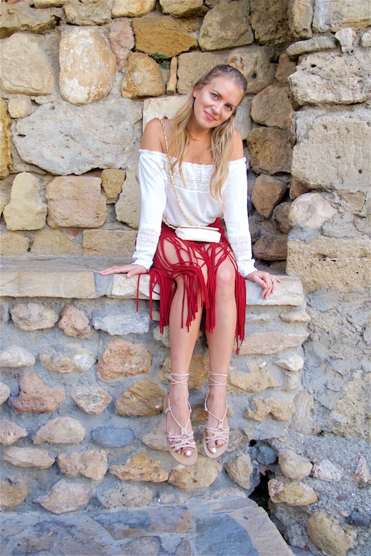 Fringe Skirt. Fashion Blogger Girl by Style Blog Heartfelt Hunt. Girl with blond half-up half-down knot wearing a red fringe skirt, white off-shoulder top, vintage Chanel bag and lace up sandals.