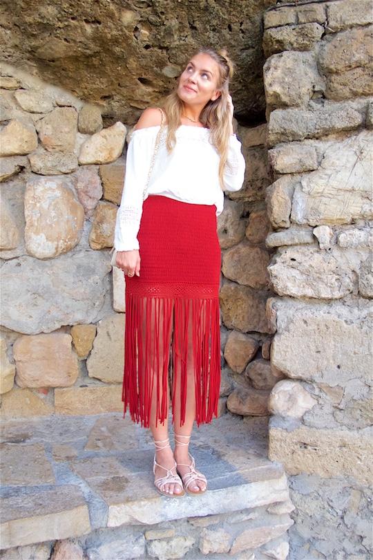 Fringe Skirt. Fashion Blogger Girl by Style Blog Heartfelt Hunt. Girl with blond half-up half-down knot wearing a red fringe skirt, white off-shoulder top, vintage Chanel bag and lace up sandals.