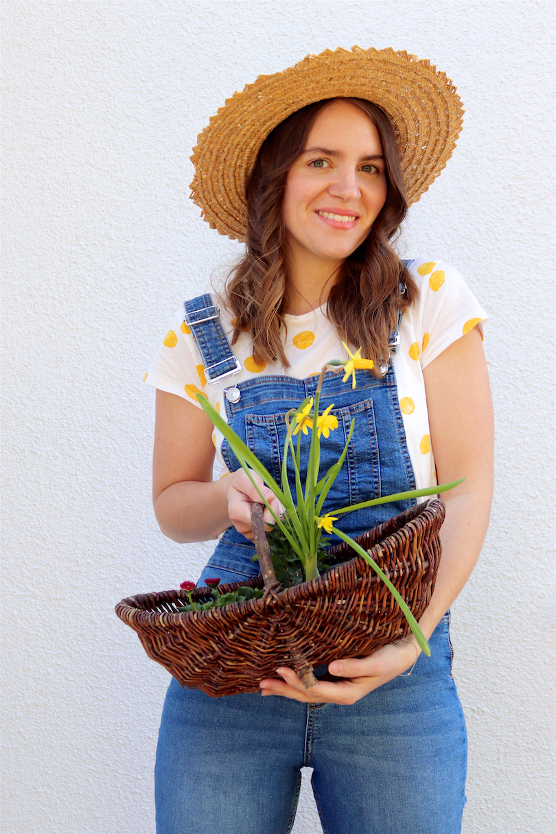 Gardening. Fashion and Style Blog Girl from Heartfelt Hunt. Girl with blonde, loose curls wearing a straw hat, yellow polka dot tee and denim overall.
