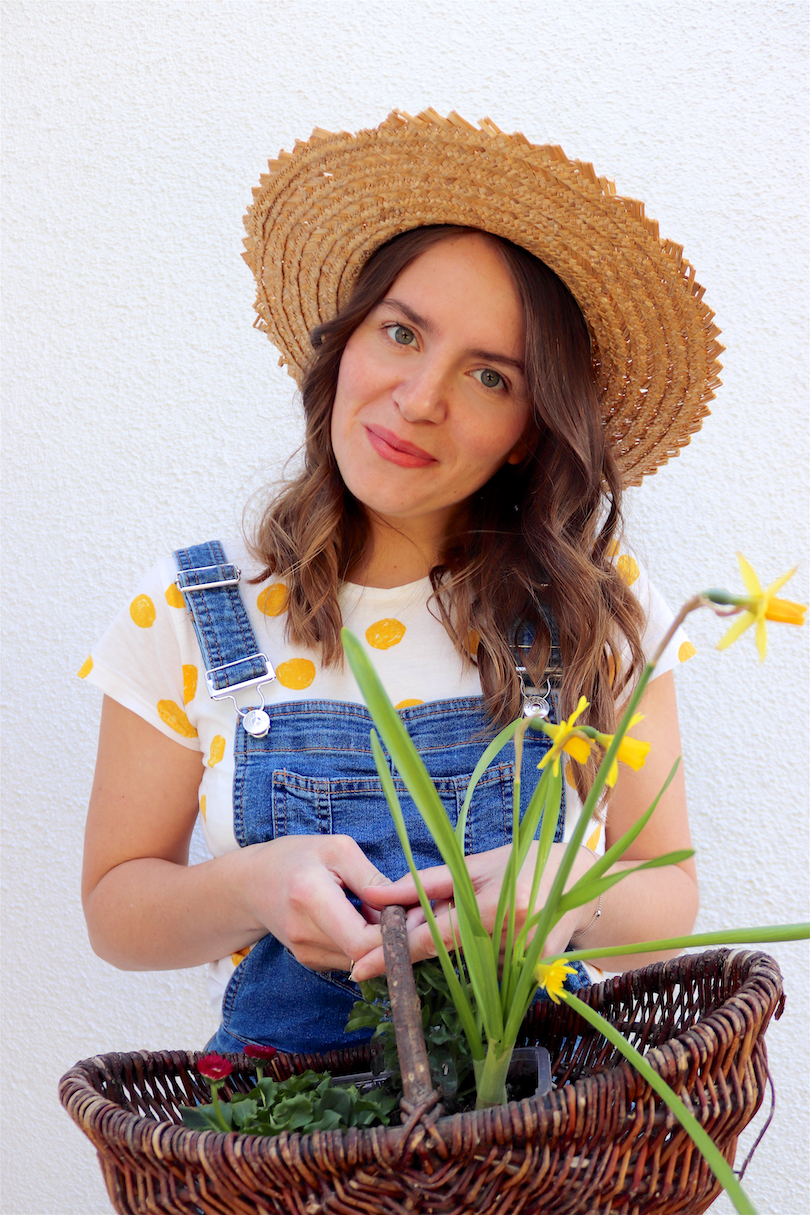 Gardening. Fashion Blogger Girl by Style Blog Heartfelt Hunt. Girl with blond, loose curls wearing a straw hat, yellow polka dot tee and denim overall.