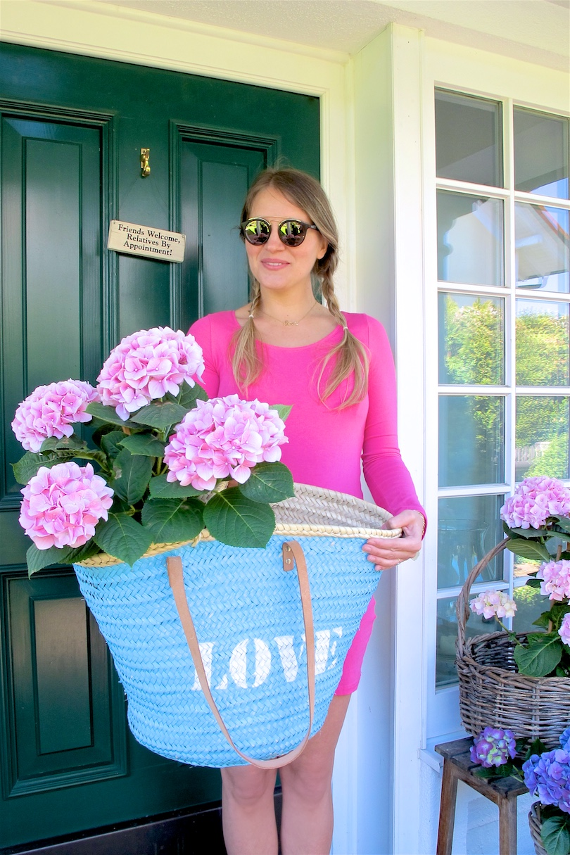 Gender Reveal. Fashion and Style Blog Girl from Heartfelt Hunt. Girl with blonde pigtail braids wearing a pink dress, basket bag, Ray-Ban sunglasses and Converse sneakers.