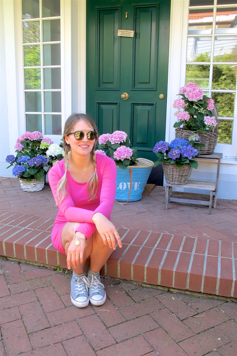 Gender Reveal. Fashion Blogger Girl by Style Blog Heartfelt Hunt. Girl with blond pigtail braids wearing a pink dress, basket bag, Ray-Ban sunglasses and Converse sneakers.