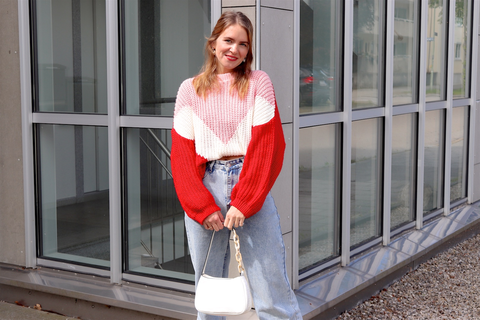 Geometric Pattern Sweater. Fashion Blogger Girl by Style Blog Heartfelt Hunt. Girl with blond half-up half-down hairstyle with scrunchie wearing a geometric pattern sweater, wide leg jeans, white 90s bag and red mules.