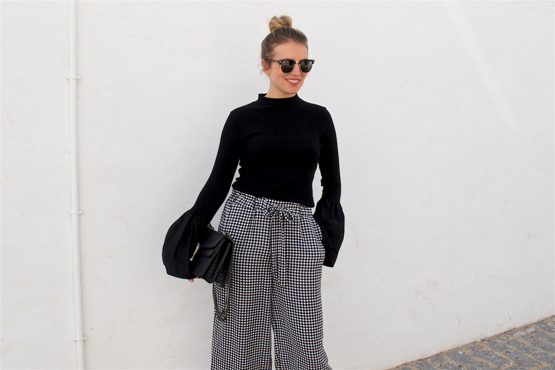 Gingham Culottes. Fashion Blogger Girl by Style Blog Heartfelt Hunt. Girl with blond high bun wearing gingham culottes, top with trumpet sleeves, Ray-Ban sunglasses, bag and lace up ballet flats.