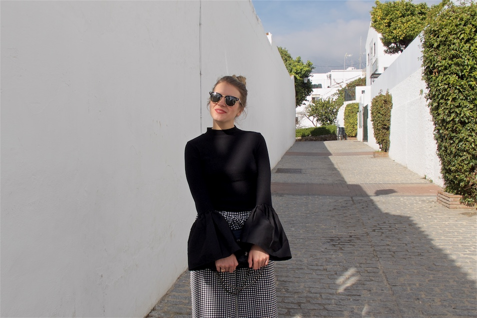 Gingham Culottes. Fashion and Style Blog Girl from Heartfelt Hunt. Girl with blonde high bun wearing gingham culottes, top with trumpet sleeves, Ray-Ban sunglasses, bag and lace up ballet flats.