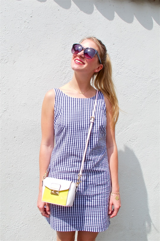 Gingham Dress. Fashion Blogger Girl by Style Blog Heartfelt Hunt. Girl with high ponytail wearing a backless gingham dress, color blocked bag, sunglasses and sandals.