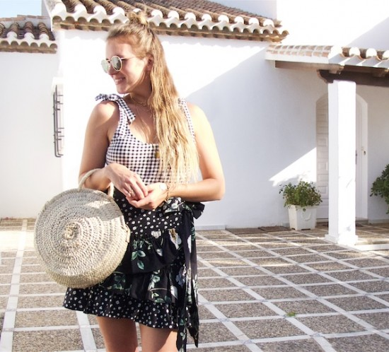 Gingham Floral. Fashion Blogger Girl by Style Blog Heartfelt Hunt. Girl with blond long hair wearing a gingham top with bows, floral skirt, Ray-Ban sunglasses, round straw bag and black sandals.