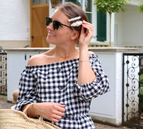 Gingham Off Shoulder Top. Fashion Blogger Girl by Style Blog Heartfelt Hunt. Girl with blond low messy bun and pearl hair clips wearing a gingham off shoulder top, Ray-Ban sunglasses, floral ruffled skirt, straw bag and black sandals.