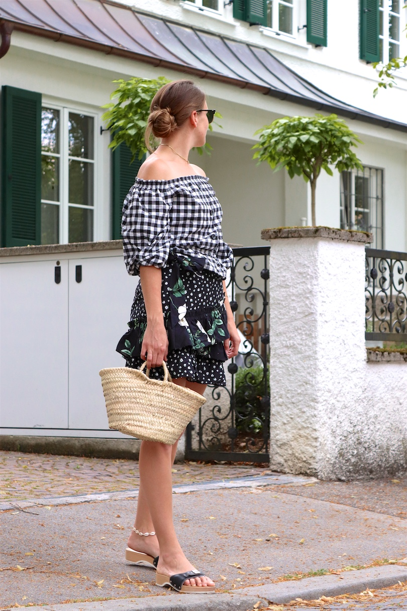 Gingham Off Shoulder Top. Fashion and Style Blog Girl from Heartfelt Hunt. Girl with blonde low messy bun and pearl hair clips wearing a gingham off shoulder top, Ray-Ban sunglasses, floral ruffled skirt, straw bag and black sandals.