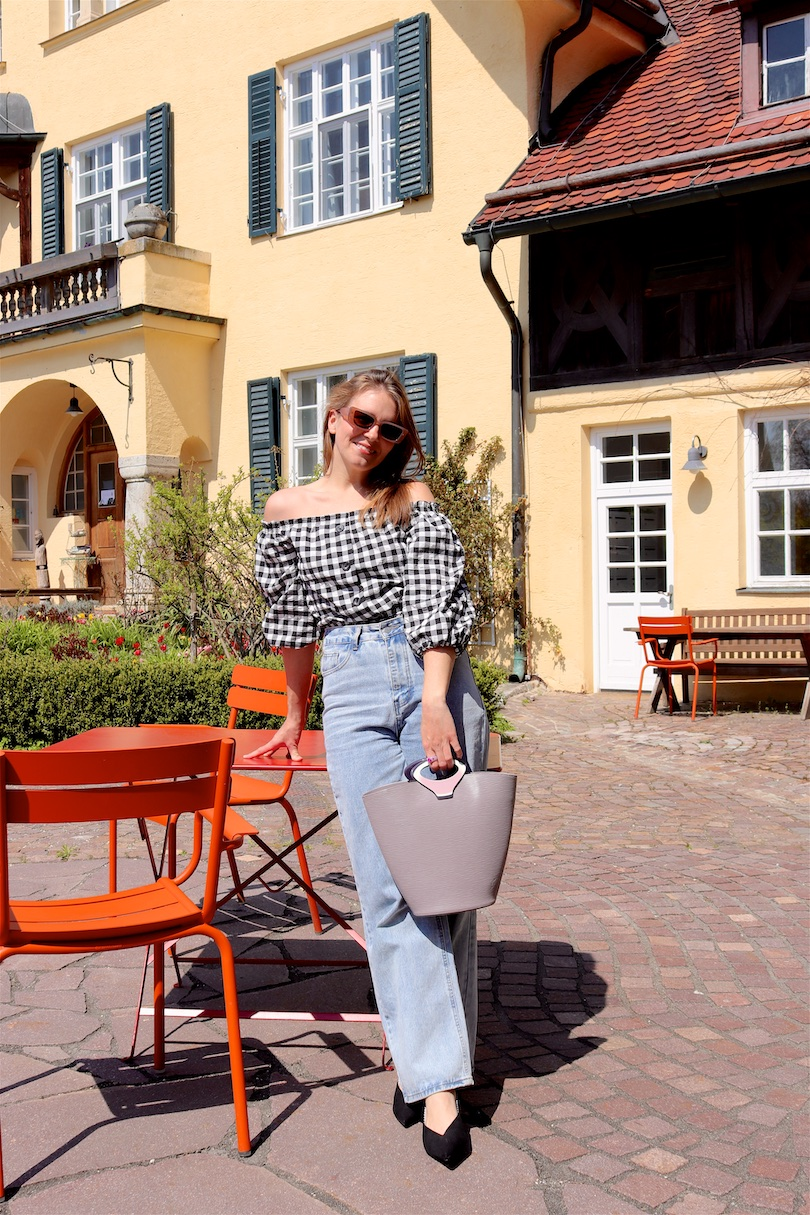 Gingham Spring Tops. Fashion and Style Blog Girl from Heartfelt Hunt. Girl with blonde hair wearing a gingham spring top, wide leg jeans, slim sunglasses, vintage Louis Vuitton bag and pointed toe mules.