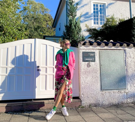 Green Pink. Fashion Blogger Girl by Style Blog Heartfelt Hunt. Girl with blond hair wearing a green sweatshirt, pink blazer, floral dress, pink sunglasses, pink mini bag, green socks and white Nike sneakers.