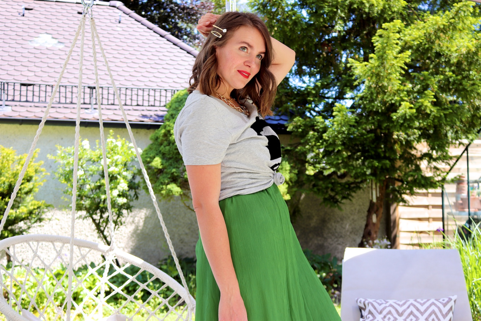 Green Vibes. Fashion Blogger Girl by Style Blog Heartfelt Hunt. Girl with blond loose waves and pearl and gold hair clip wearing a green dress, graphic tee, statement necklace, round straw bag and straw sandals with pompons.