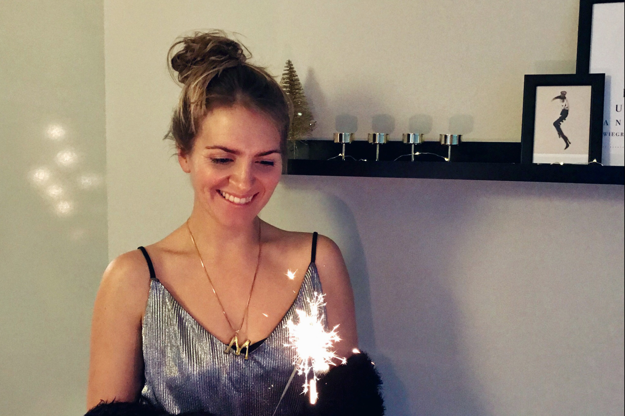 Happy New Year 2019. Fashion Blogger Girl by Style Blog Heartfelt Hunt. Girl with blond, high messy bun wearing a silver pleated dress and a chenille cardigan wishing you a happy New Year for 2019.