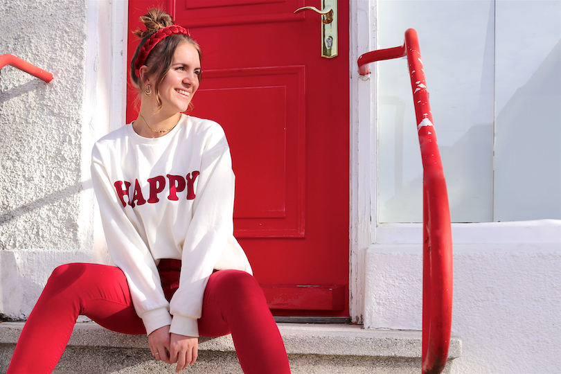 Happy Sweatshirt. Fashion Blogger Girl by Style Blog Heartfelt Hunt. Girl with blond high messy bun and a red braided headband wearing a 'Happy' sweatshirt, red pants, snake print bag, belt and black Timberland boots.