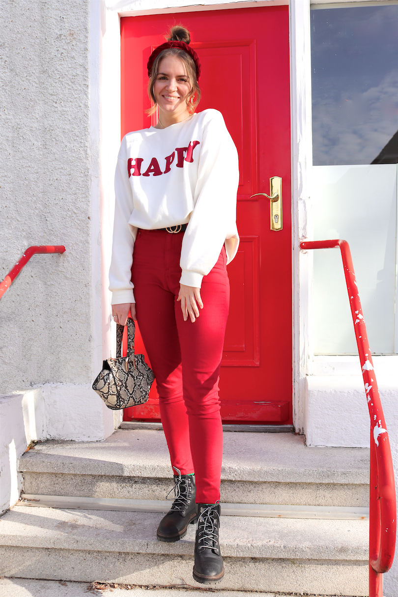 Happy Sweatshirt. Fashion and Style Blog Girl from Heartfelt Hunt. Girl with blonde high messy bun and a red braided headband wearing a 'Happy' sweatshirt, red pants, snake print bag, belt and black Timberland boots.