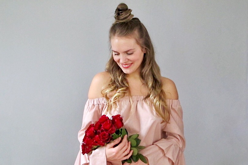 Happy Valentines Day. Fashion and Style Blog Girl from Heartfelt Hunt. Girl with blonde, loose curls and half-up half-down bun wearing a light pink off shoulder blouse with ruffled sleeves.