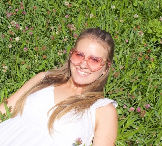 Heart Shaped Sunnies. Fashion Blogger Girl by Style Blog Heartfelt Hunt. Girl with blond half-up half-down hairstyle with a dutch braid wearing heart shaped sunnies, a white summer dress and straw bag.