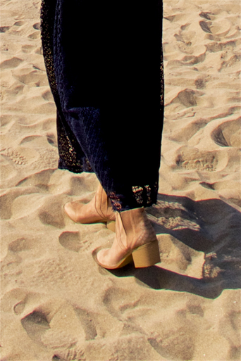 Fashion and style blogger girl's dark-blue lace dress and nude boots in closeup view on the beach