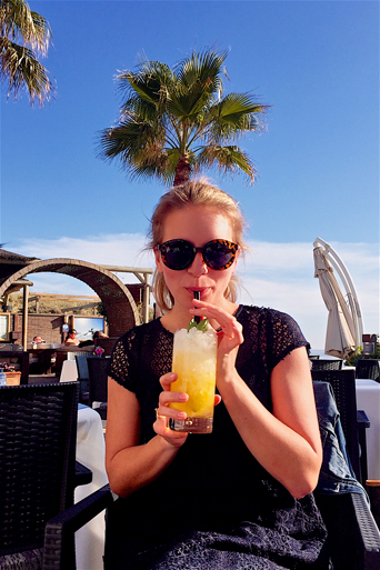 Blond fashion and style blogger girl drinking a yummy mojito in the sunshine, wearing a dark-blue lace dress and sunglasses
