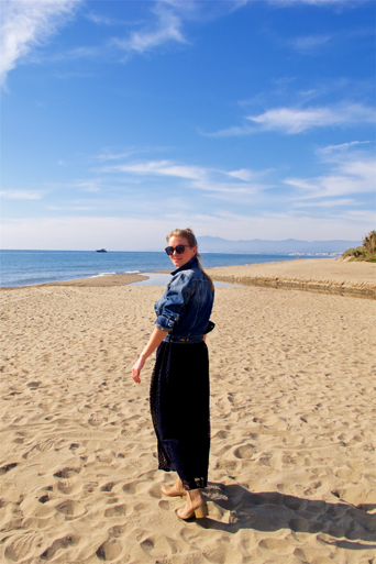 Blond fashion and style blogger girl looking back over her shoulder, wearing a dark-blue lace dress, denim jacket and sunglasses on the beach