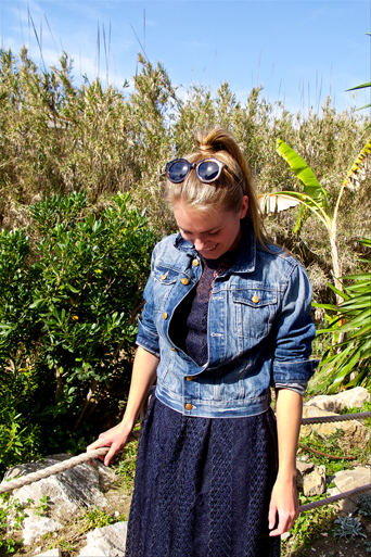 Blond fashion and style blogger girl wearing a dark-blue lace dress, denim jacket and sunglasses