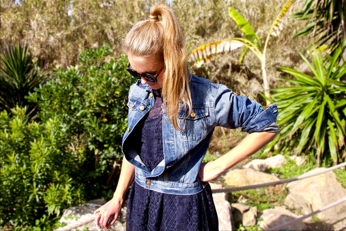 Blonde fashion and style blogger girl with high ponytail wearing a dark-blue lace dress, denim jacket and sunglasses