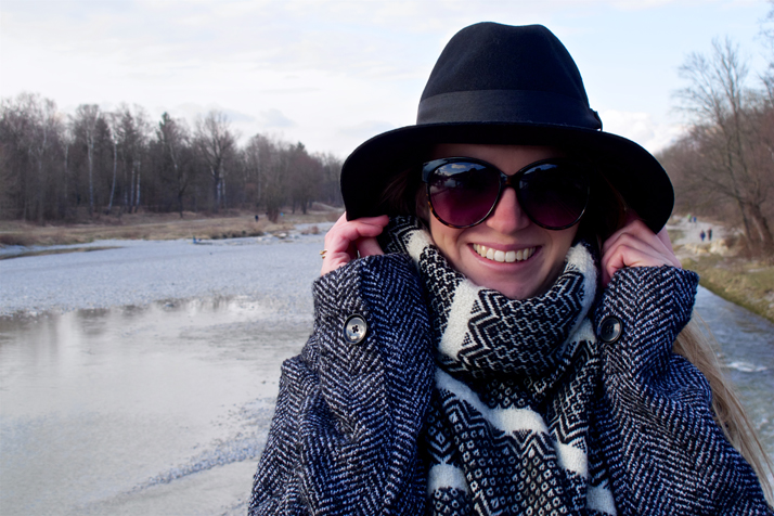 Smiling blonde fashion and style blogger girl in closeup view holding on to her hat, wearing an oversized jacket, black hat, sunglasses and a black and white scarf