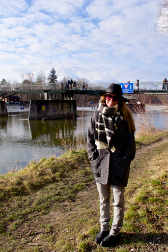 Smiling blond fashion and style blogger girl wearing an oversized jacket, grey jeans, black boots, black hat, sunglasses and a black and white scarf