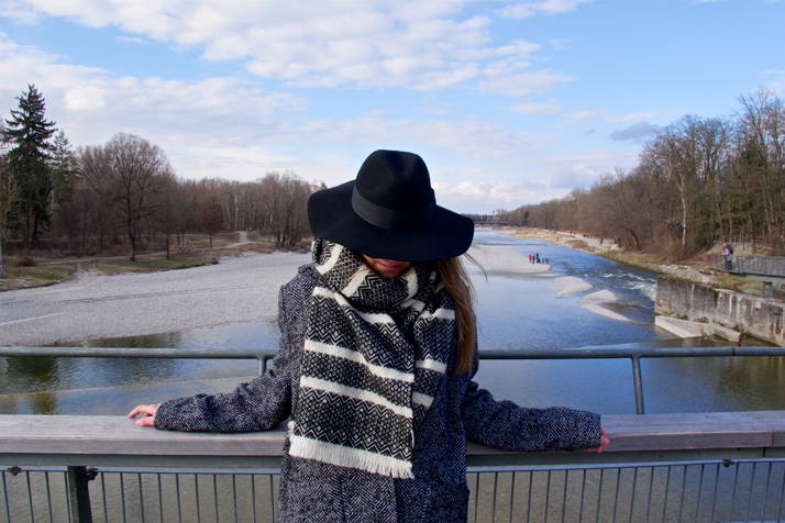 Blond fashion and style blogger girl looking down, wearing an oversized jacket, black hat, sunglasses and a black and white scarf