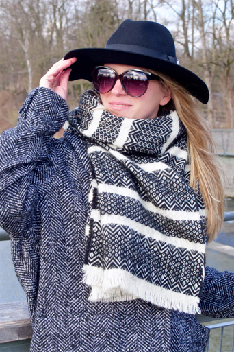 Smiling blonde fashion and style blogger girl in closeup view wearing an oversized jacket, black hat, sunglasses and a black and white scarf