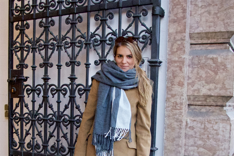 Blonde fashion blogger girl with sunglasses, oversized scarf and camel coat standing in front of a gate